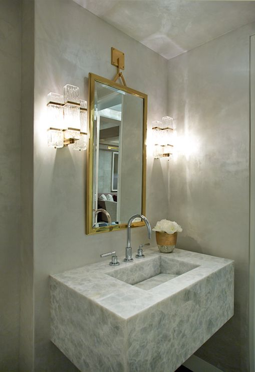 glam bathroom features gray walls lined with a white onyx vanity and sink paired with a gooseneck faucet under a gold vanity mirror hanging from gold hook