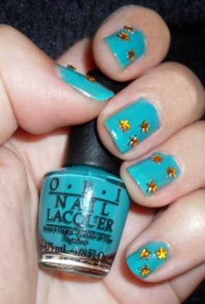 Gold rhinestones on turquoise background.