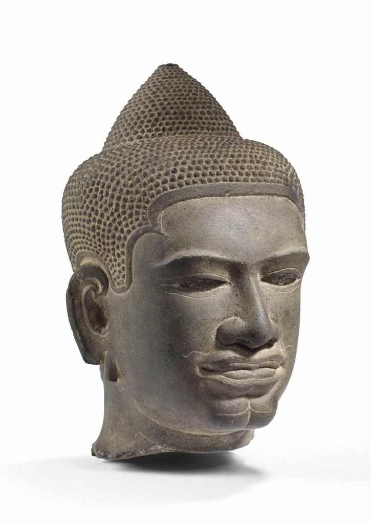 RARE TETE DE BOUDDHA SHAKYAMUNI EN GRES POLI CAMBODGE, KHMER, EPOQUE BAPHUON, XIEME SIECLE Son visage aux yeux en amandes surmontés de sourcils légèrement arqués est serein. Ses lèvres charnues sont surmontées d'une moustache délicatement incisée. Ses cheveux bouclés sont surmontés de l'ushnisha. Hauteur : 21 cm. (8 ¼ in.), socle