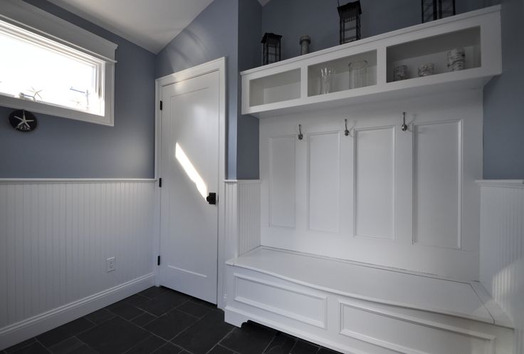 Mudroom with slate floor tile, wainscoting on walls, and custom built-in bench seat with piano ...