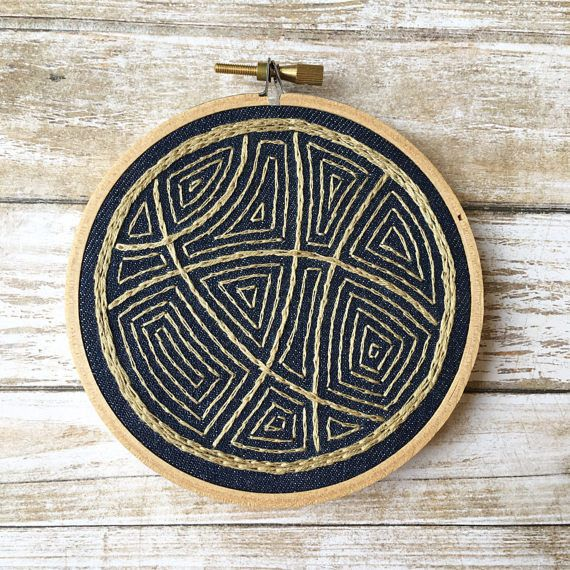 This is an embroidered wall hanging, framed in a 4 inch wooden embroidery hoop  The abstract design was hand drawn and then hand embroidered onto navy blue fabric. I have used gold colored DMC embroidery floss to stitch this design. I have hand stitched a circle of dark grey felt onto the back of the hoop. The felt backing protects the stitching, and gives the piece a nice, neat finish.  If you would like me to add a small loop of brass wire for easy hanging, please be sure to select the…