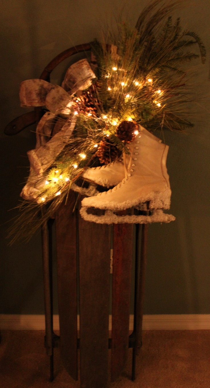 Cute snow sled with vintage ice skates and lights.