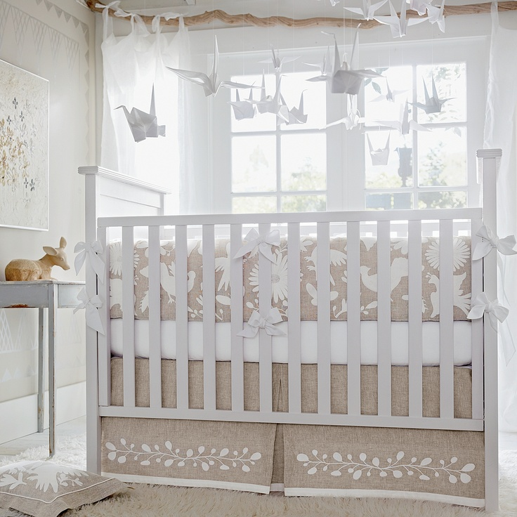 Inspired by vintage Mexican folk art, the naturalistic motif brings a little magic to the nursery. Flat-style bumper in flax linen with embroidery on both sides and white sateen piping and ties; zippered slipcover removes easily for washing. Single box-pleated skirt in flax linen with an embroidered band and white sateen trim.