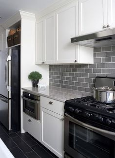 light gray subway tile backsplash with dark grey tile floors and white  cabinets. love this