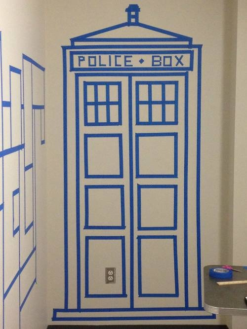 TARDIS on the wall with painter's tape--- (^^) MUST MAKE ROOM ON DORM WALL TO DO THIS... Or shall I convince my roommates to let me do it to our dorm room door... hmm...