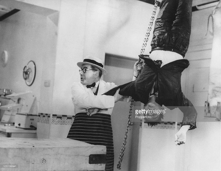 English comedy actors Edward Chapman (1901 - 1977, left) and Norman Wisdom (1915 - 2010), as Mr. Grimsdale and Norman Pitkin, in a scene from 'A Stitch In Time', directed by Robert Asher, 1963. In the scene, Pitkin has been frozen stiff and is being hung up in a butcher's shop to thaw out.
