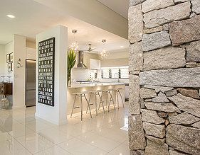 Rustic stone wall contrasting with contemporary white gloss kitchen