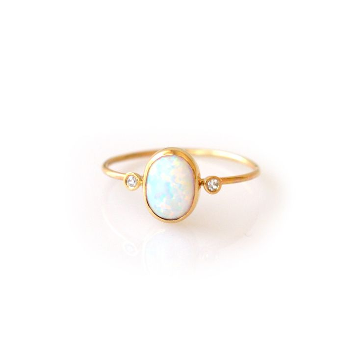 -solid 14kt gold -2pt diamonds (clarity VS 1/2) (size 0.25 carats) -genuine 8x6mm opal -1mm ring band A simply gorgeous ring with a divine combination of opals and diamonds. Destined to become your ev