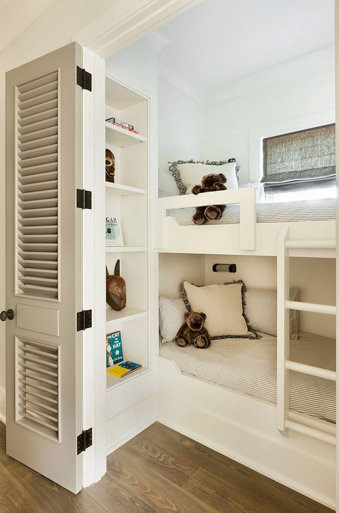 Smartly designed small bunk room with bookcase for extra storage and louvered doors to add privacy. Webb Interiors