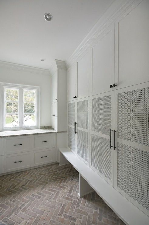 Fantastic mudroom features wall of built-in cabinets stacked over cubbies used to house shoes atop herringbone brick pavers.