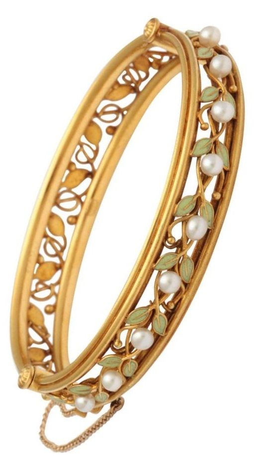 An Arts and Crafts Enamel, Pearl and Gold Bangle Bracelet, circa 1910. Designed as an openwork vine of 18k gold and green enamelled leaves, the upper half enhanced with fresh water pearls. The gold bracelet opens on a hinge and is fitted with a plunger clasp. With maker's mark A.P. #ArtsCrafts #bangle #bracelet
