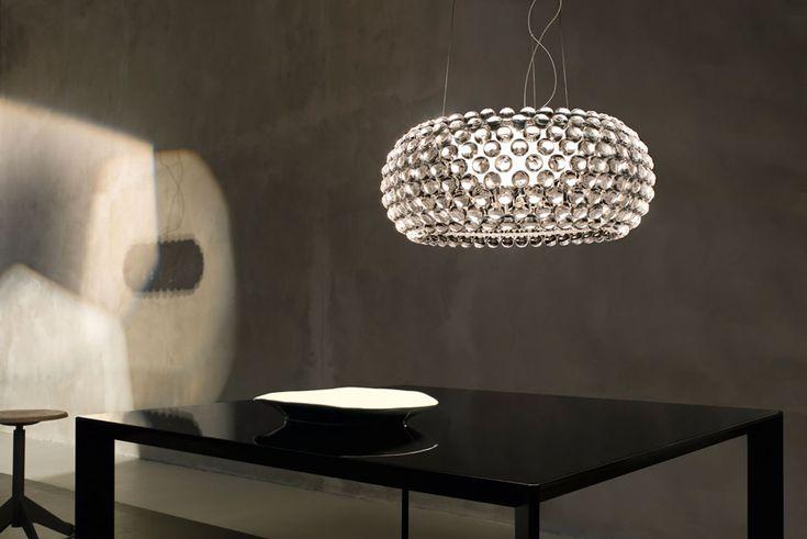 Caboche Grande, pendel formgiven av Patricia Urquiola och Eliana Gerotto för Foscarini. Lampans skärm består av sfärer av transparent polymetylmetakrylat som omsluter den inre skärmen i vitt, satinborstat glas. Den inre skärmen skapar ett trivsamt ljus som reflekteras och sprids genom de kristallika yttre sfärerna. En elegant takkopp i förkromad metall ingår.