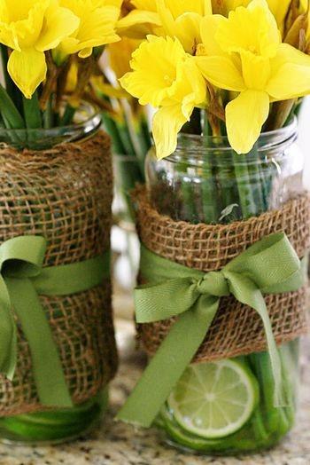 Mason jar vase. Burlap ribbon, smaller ribbon in middle (grey turquise, maybe lace), fake flowers. LOVE.