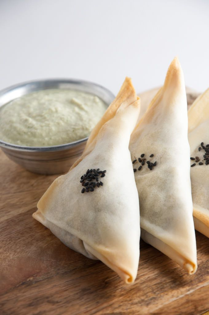 Recipe for vegan, baked Samosas filled with potatoes and spinach. They are a served with a creamy Cilantro Lemon Dip. Uses Spring Roll Wrappers....