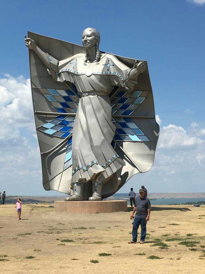 This went up in South Dakota! Dignity is a sculpture on a bluff overlooking the Missouri River near Chamberlain, South Dakota.The 50-foot high stainless steel statue, by South Dakota artist laureate Dale Lamphere, depicts an Indigenous woman in Plains-style dress receiving a star quilt. According to Lamphere, the sculpture honors the culture of the Lakota and Dakota peoples who are indigenous to South Dakota.Assisting Lamphere were sculptors Jim Maher, Andy Roltgen, and Grant Standard.