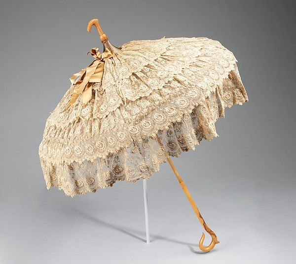 Parasol Date: 1880–90 Culture: American Medium: silk, wood, metal. Parasols were for show, carried as an accessory to complete a toilette. This example is fitted with a crook at top so it could be carried with the canopy down for a more elegant line than carrying it from the handle end. In addition, this shows off the tiers of feminine ruffles.