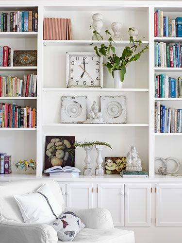 Fill a bookcase with treasured finds! The one in this living room houses oil paintings from the 1930s and a midcentury Bulova wall clock. #decorating
