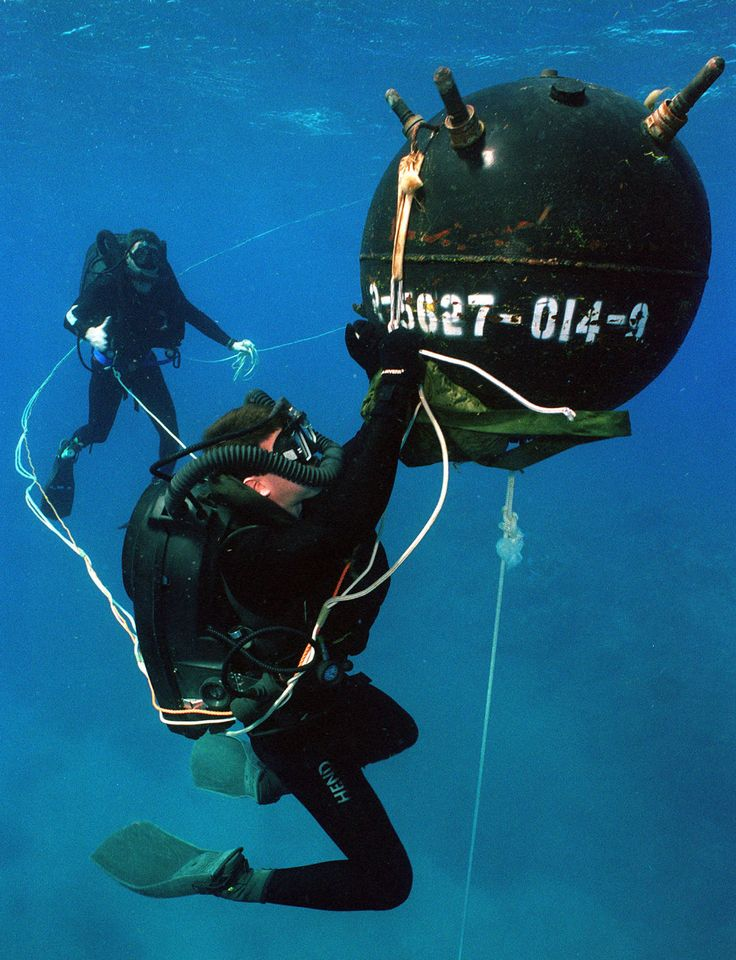 """A U.S. Navy explosive ordnance disposal (EOD) diver attaches an inert """"Satchel Charge"""" to a training mine, during exercises in waters off Naval Base Guantanamo Bay, Cuba."""