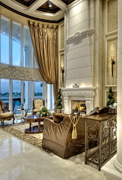 """Upon entering the grand entry doors of the """"Padova"""", you are greeted by a two-story grand salon with a stone fireplace and curved glass wall that overlooks the pool and view beyond. Crafted in transitional Spanish-Mediterranean flair. #luxuryhomeplans #luxuryhouseplans www.saterdesign.com"""