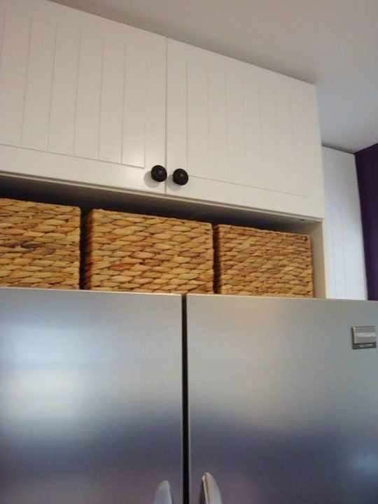 Ideas for Using that Awkward Space Above the Fridge.... great place for extra glassware and company dishes