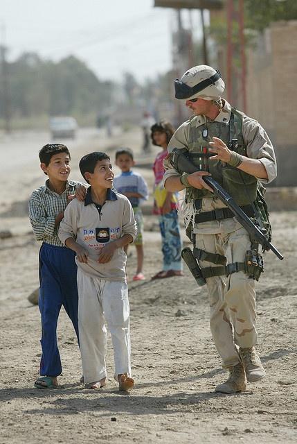 US Marine chats to children.  A US Marine on patrol chats to Iraqi children