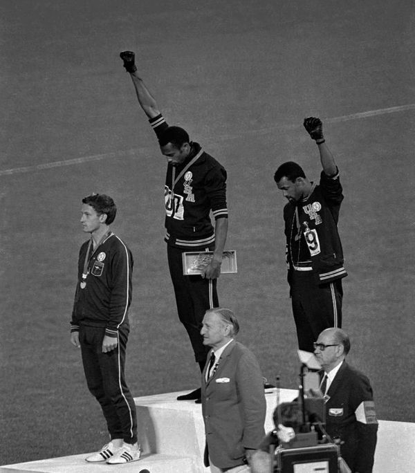 This iconic photograph is from the 1968 Olympics. What Tommie Smith and John Carlos did was a 'black power' salute on the podium. The idea of this salute was Peter Norman's who did not perform the salute himself. Norman, an Australian, was later blacklisted from appearing at any future Olympics because he supported black rights. He was ostracized and went into severe depression and took to substance abuse.