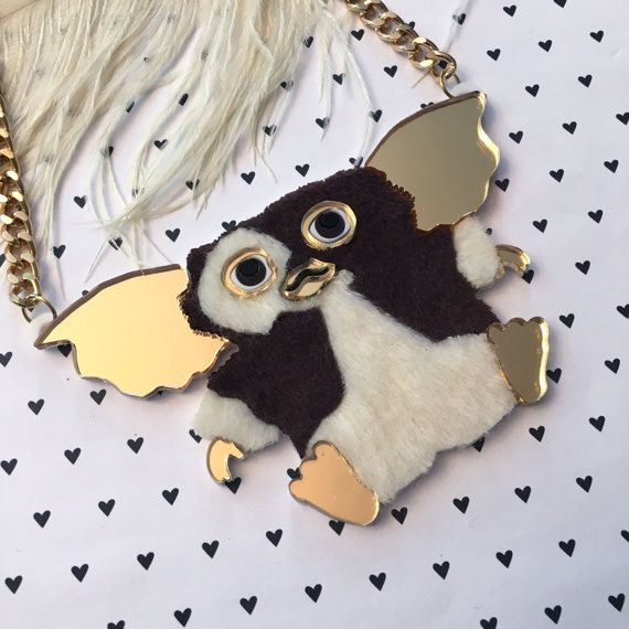 There are just three rules you have to remember for owning this necklace- 1. No bright light 2. Dont get him wet, and 3. Never feed him after midnight, no matter how much he begs. Bright light hurts him, and sunlight can kill him.  This adorable necklace was cut from a mix of furry fabric and mirrored and opaque acrylic. The pendant measures 4.5 wide by about 2 & 3/4 high.  The necklace hangs from a thick, gold chain that measures 16 long with a 3 extender chain so you can decide whi...