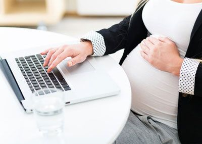 Heavily pregnant woman working on laptop