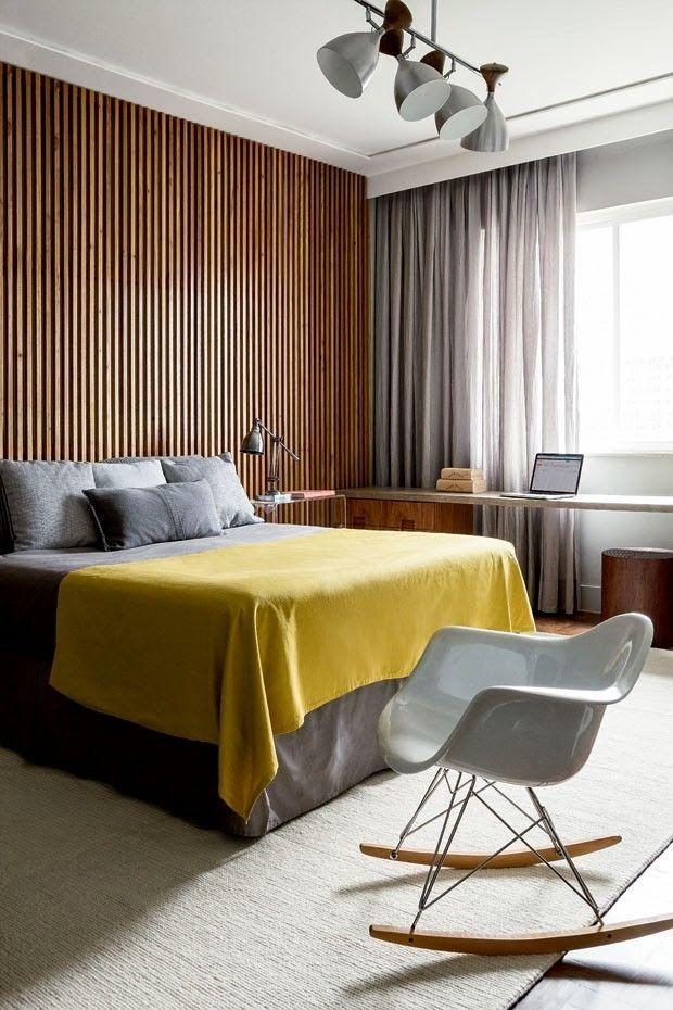 Quarto neutro com destaque para a manta amarela e parede com revestimento de madeira