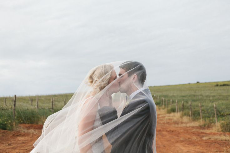 Bride & Groom kissing under brides chapel length veil - Le Sueur Photography