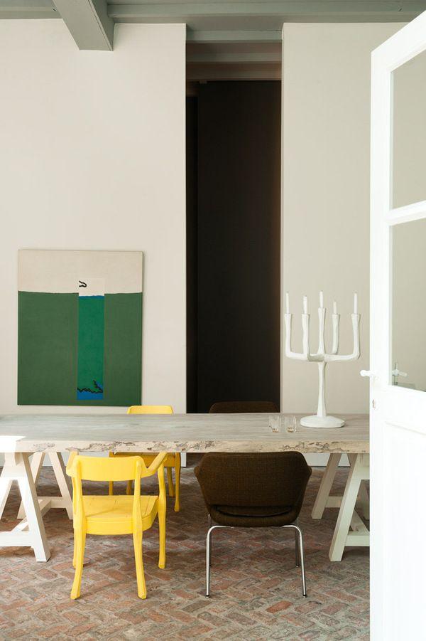 Design gallerie Valerie Traan in Antwerpen: Gebroken-witte muren met hier en daar een accent, zoals hier de groene schilderij en de verschillende gekleurde stoelen.