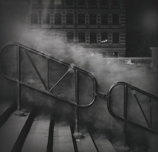 """Alexey Titarenko. Saint-Petersbourg. Foule montant un escalier. Cette image démontre que la photographie n'est pas """"objective"""" : elle voit le temps à l'œuvre, contrairement à nous qui n'""""imprimons pas"""". L'exposition de 30 secondes transforme les têtes en vapeur blanche, les pieds en vapeur noire ; quelques mains sont nettes sur la rampe (les mains étant la partie du corps laissée le plus longtemps immobile). ( notice rédigée par Serge Sautereau. http://serge-sautereau.com )"""
