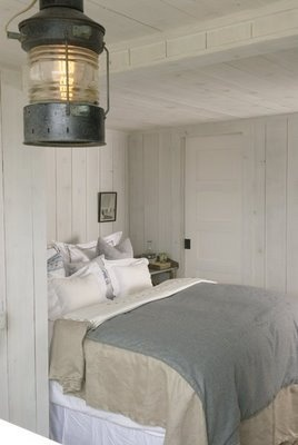 Floor to ceiling neutral wood paneled cottage bedroom.