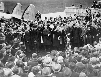 Neville Chamberlain holding the paper containing the resolution to commit to peaceful methods signed by both Hitler and himself on his return from Munich. He is showing the Anglo-German Declaration to a crowd at Heston Aerodrome on 30 September 1938.