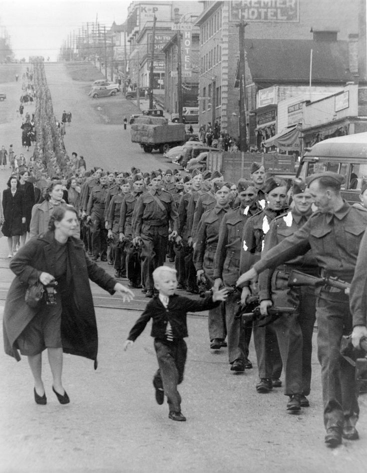 """Wait For Me Daddy,"" October 1, 1940: A line of soldiers march in British Columbia on their way to a waiting train as five-year-old Whitey Bernard tugs away from his mother's hand to reach out for his father."