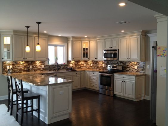 U shaped kitchen with peninsula design with American Woodmark cabinets; Savannah Maple white with hazelnut glaze... Mosaic glass and stone tile. Stainless steel appliances... My dream kitchen come alive.: