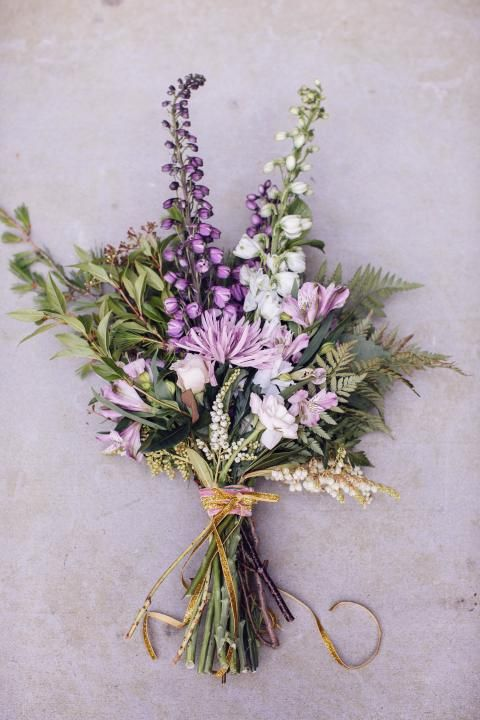 Purple flowers and greenery in an informal bouquet tied with raffia