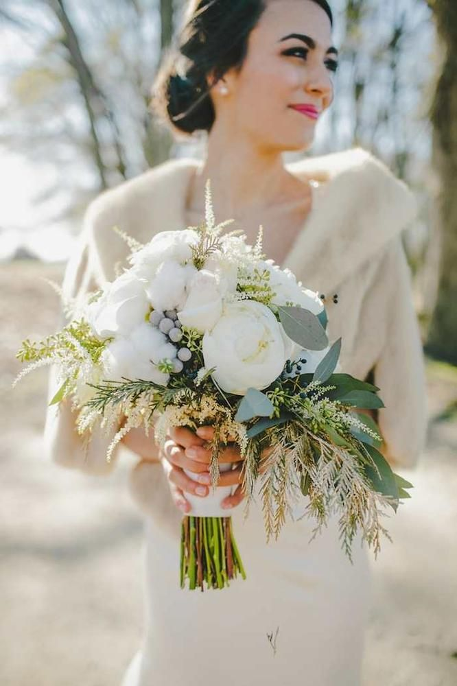 This winter bride looks gorgeous in her cropped fur jacket, and the traditional white bouquet dressed up with wintery greenery just tops off the look. We love this modern retro vibe!