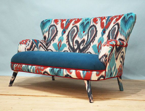 Handmade two seater sofa upholstered with beautiful Ikat print fabric and turquoise cotton fabric covering the seating area. The wood
