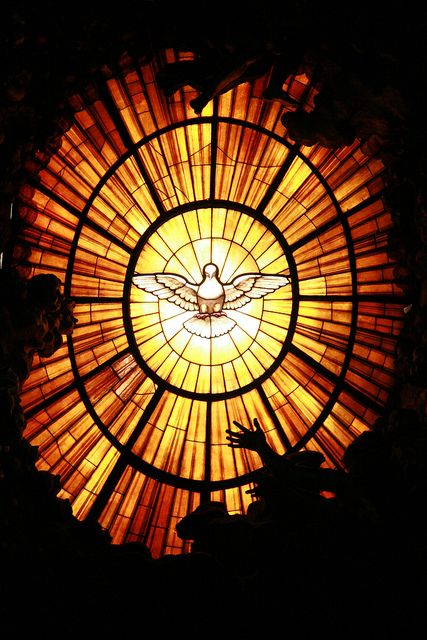 The golden colored stained glass window behind the altar in St. Peter's Cathedral in Rome.