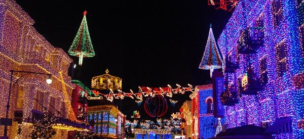 """The Osborne Family Spectacle of Dancing Lights~ Located at Hollywood Studios ~ Each evening, millions of twinkling bulbs are used to create a dazzling spectacle. The synchronized lights dance in time to a high-energy holiday symphony. Virtually every surface is illuminated. With angels flying overhead and """"snow"""" falling, it's an experience that fills visitors with holiday cheer."""