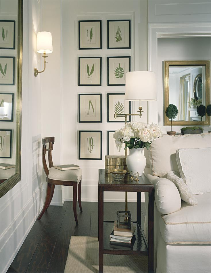 wall grouping, wood work, dark wide plank floors, trim on sofa and lighting