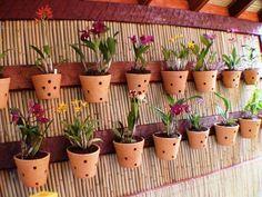 Jardim suspenso com esteira de bambu e vasos de orquídeas