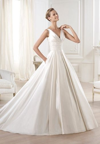 Princess bridal dress in satin. Bodice with V neck gathered under the bust with a draped sash to the