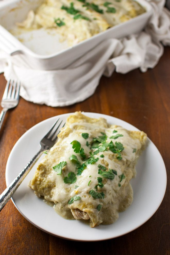 Chicken enchiladas smothered in cheese and a creamy homemade tomatillo sauce from tamingofthespoon.com.