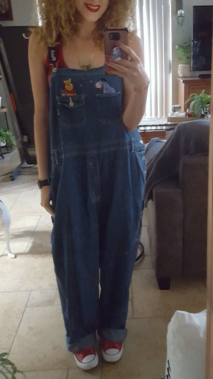 ba655257d73da 90s style grunge baggy loose-fitting Disney Winnie the Pooh overalls paired  with a red and black plaid tank top shirt and some red Converse very retro