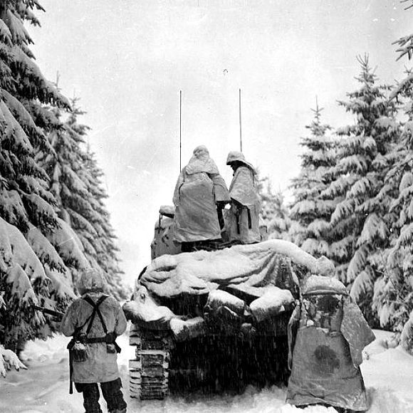 Yhdysvaltain armeijan panssarivaunu ja sotilaita etenemässä Ardennien taistelun aikana joulukuussa 1944.