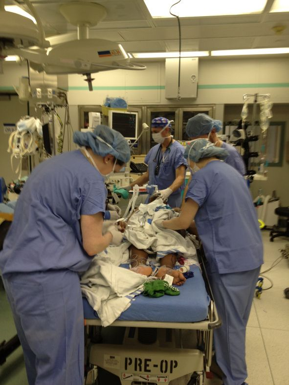Multiple Tasks to Get Ready for Spinal Fusion Case - For a spinal surgery case, the team divides up the airway, lines, neuromonitoring, and urinary catheter placement.