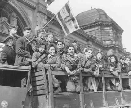 Crianças judias refugiadas reunidas na área de ocupação dos Estados Unidos na Alemanha, a caminho para a Palestina. Um refugiado segura uma bandeira sionista. Frankfurt, Alemanha, 10 de abril de 1946.