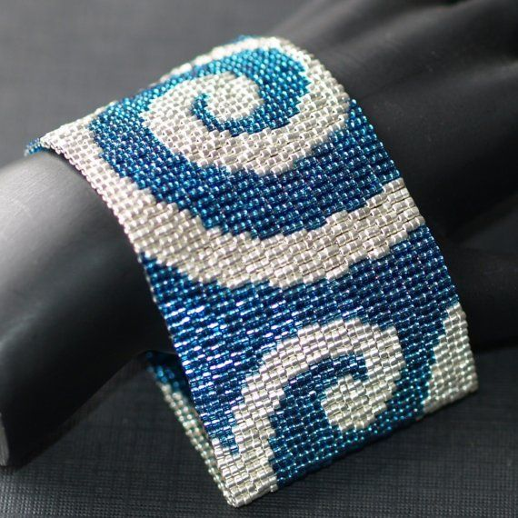 Este brazalete de beadwoven amplia es tejida con cuentas Delica japonesa en increíbles tonos de azul y plata. Una de las cosas que le da este brazalete su brillo y extra brillo es la combinación de turquesa con revestimiento de plata y perlas de plata-alineado circón azul utilizadas. Están muy cerca uno del otro en color, pero hay bastante diferencia a lo dan un aspecto único. Las plata ondas son plata galvanizada y contrastan con los granos azules maravillosamente.    Beadwoven las pulseras…